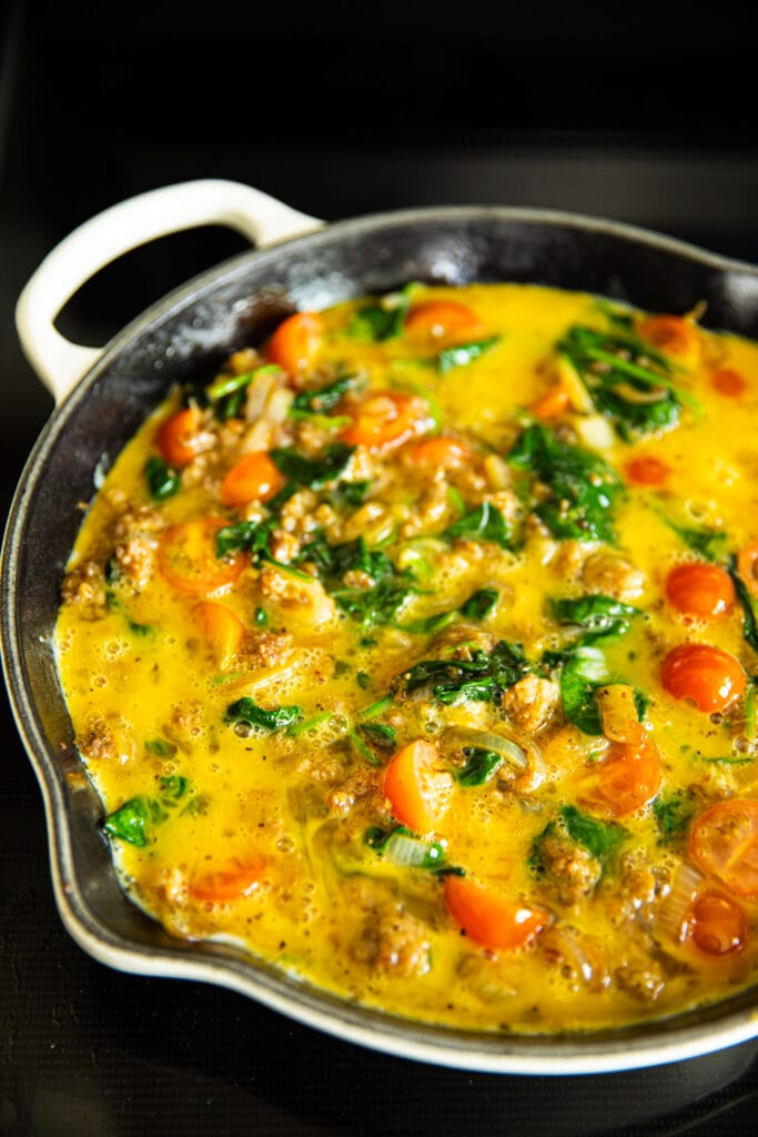 uncooked frittata in white skillet