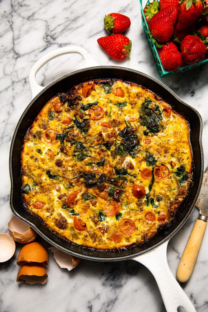 kitchen sink frittata in white skillet on marble surface