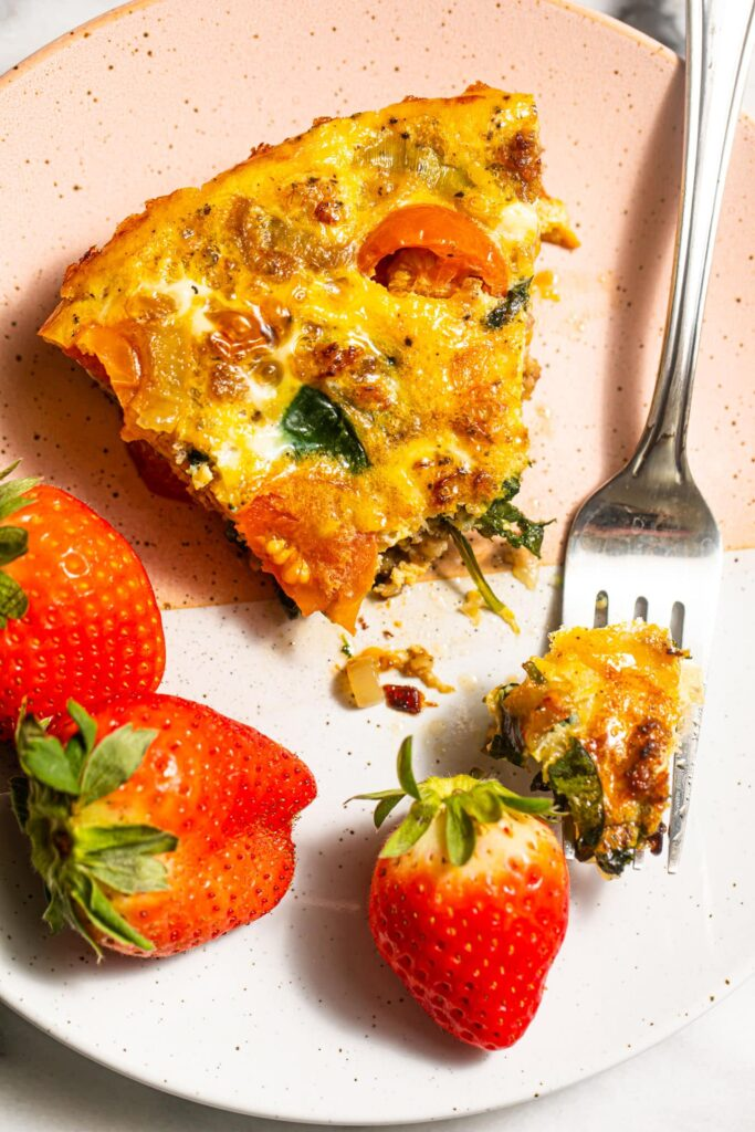 slice of frittata with strawberries on small pink and white plate