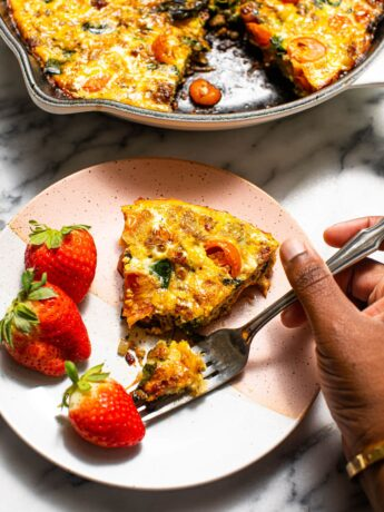 black hand with fork taking a piece of frittata on small plate