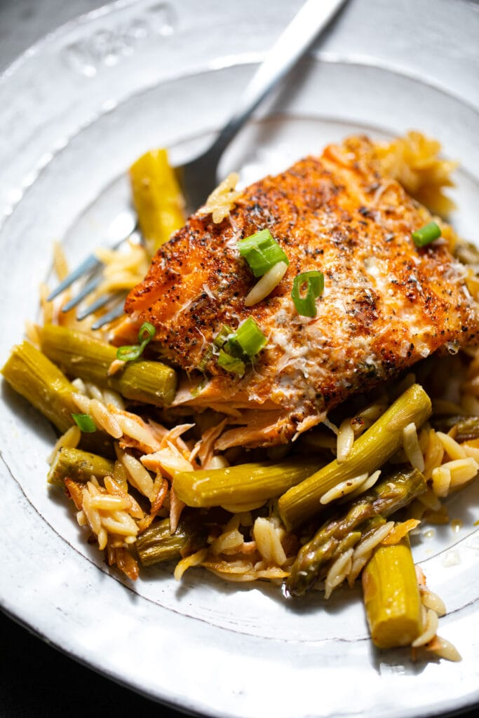 salmon with orzo and asparagus on white plate