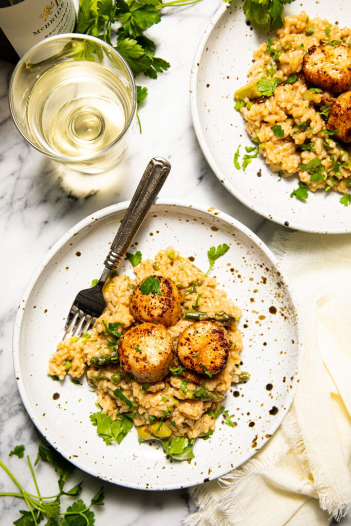 lemon butter scallops with risotto in speckled bowls on marble surface