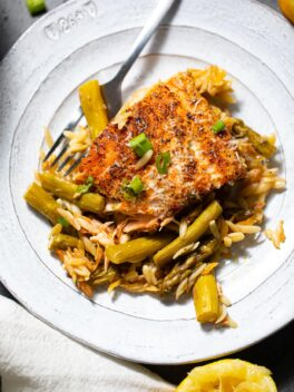 salmon on top of orzo and asparagus on white plate