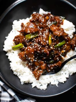 Mongolian beef on top of white rice in black bowl