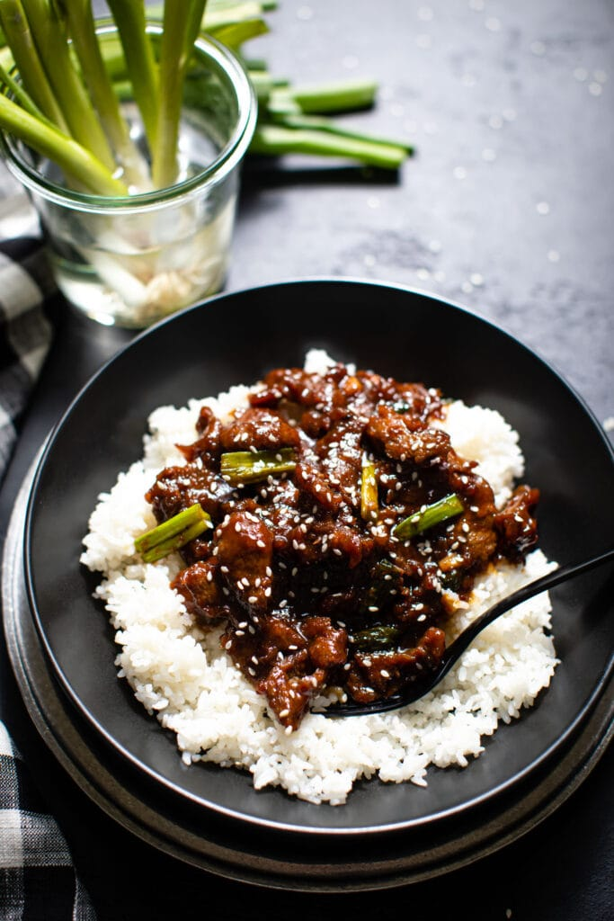 Mongolian beef on top of white rice in black bowl with scallions in a glass