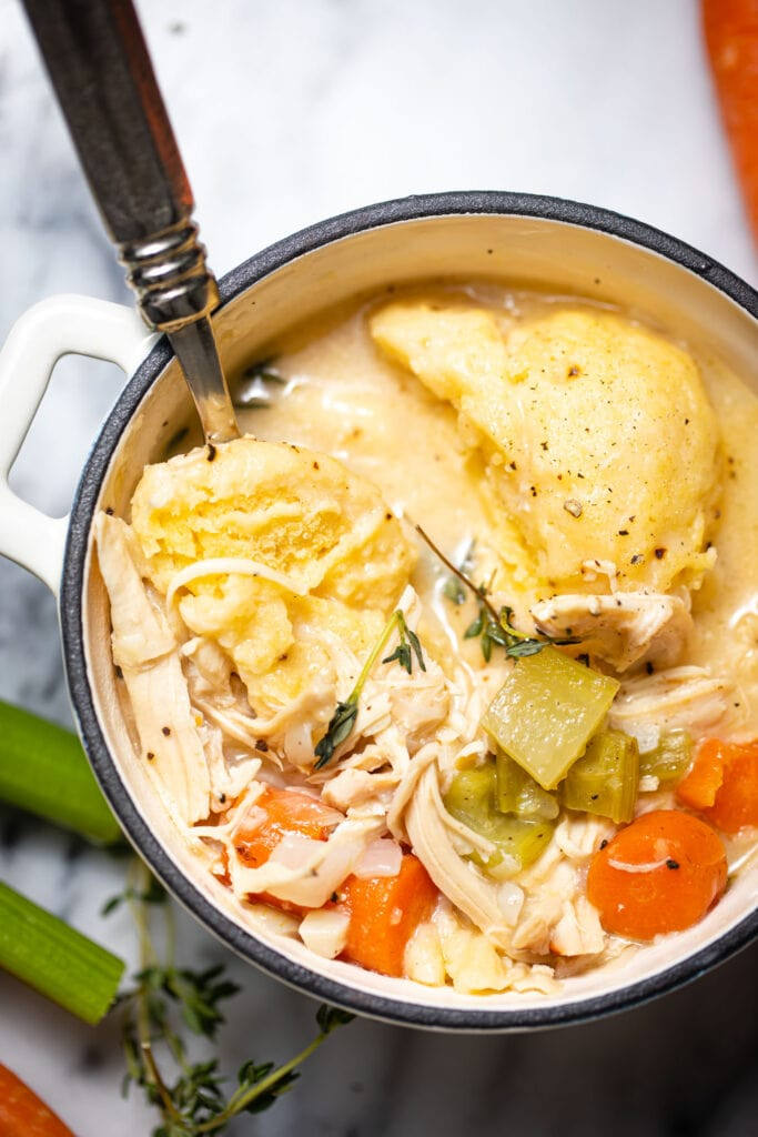 chicken and dumplings in small white pot with silver spoon