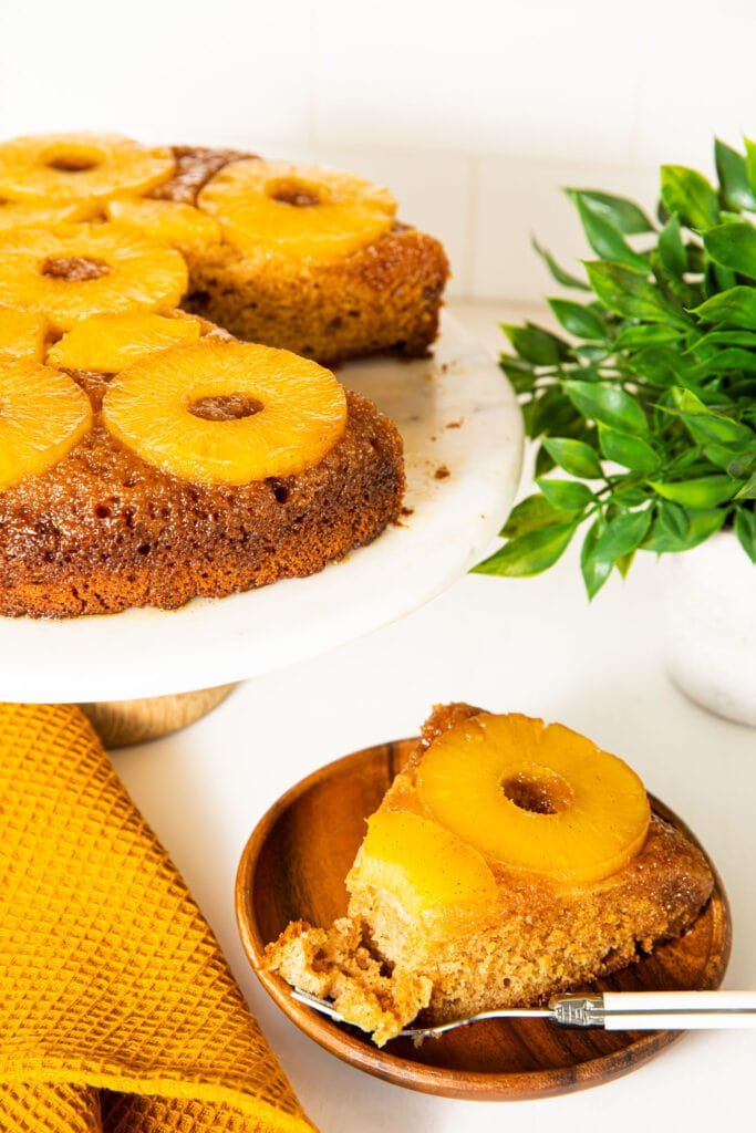 bourbon pineapple upside down cake on cake stand with cake slice on wood plate