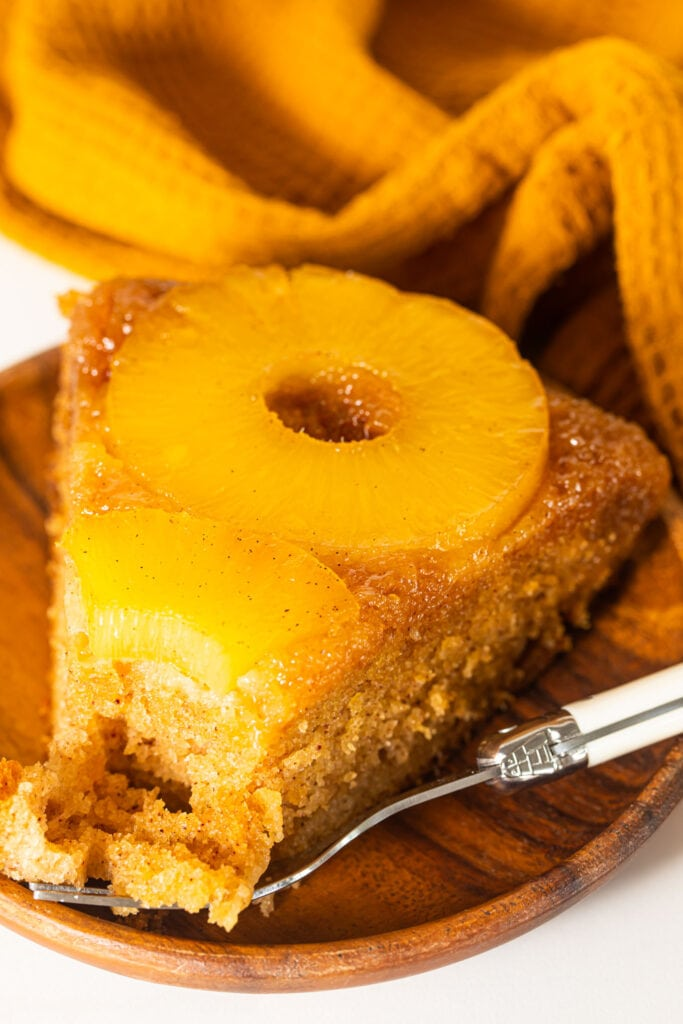bourbon upside down cake slice on wooden plate with fork