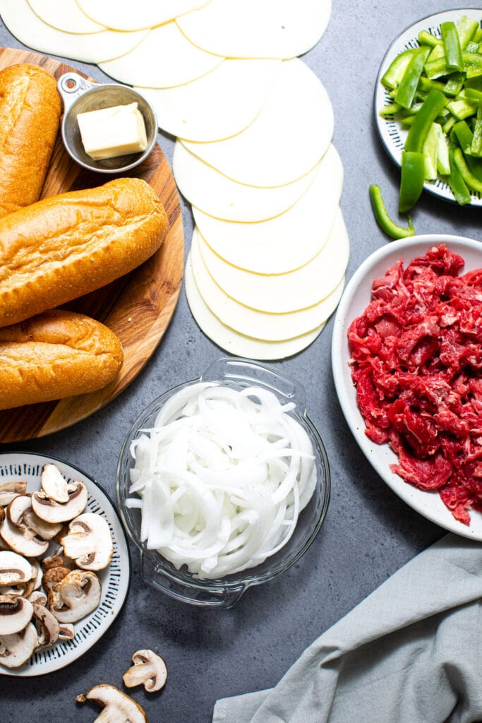 ingredients for Philly cheesesteaks on gray surface