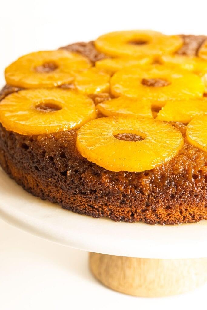 bourbon pineapple upside down cake on white cake stand