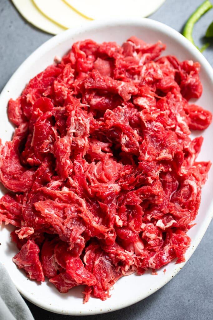 raw shredded steak on oval white plate