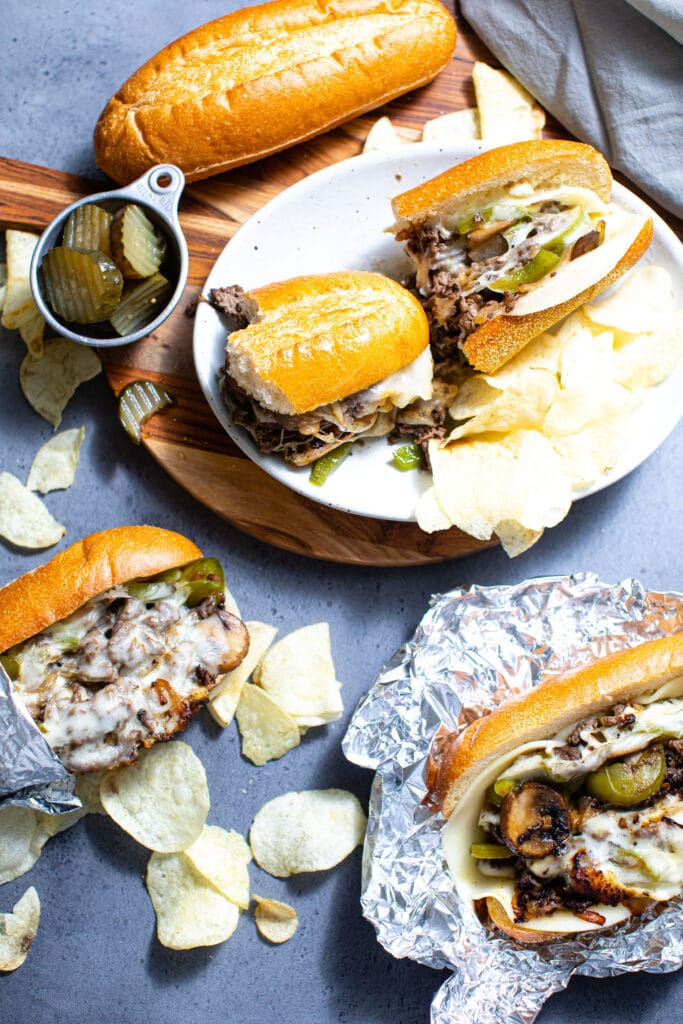 Philly cheesesteak sandwiches on wood board with chips