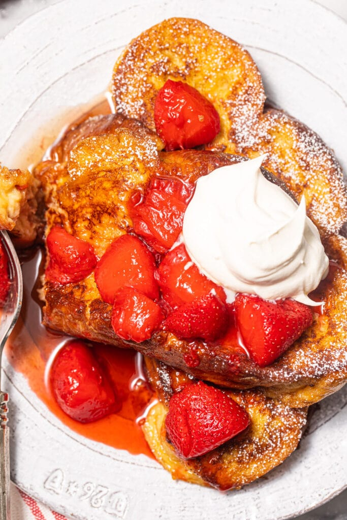 challah French toast with strawberry compote and whipped cream on white plate