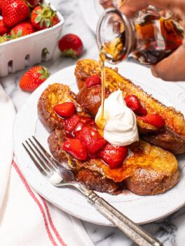 black hand pouring syrup over challah French toast with strawberry compote