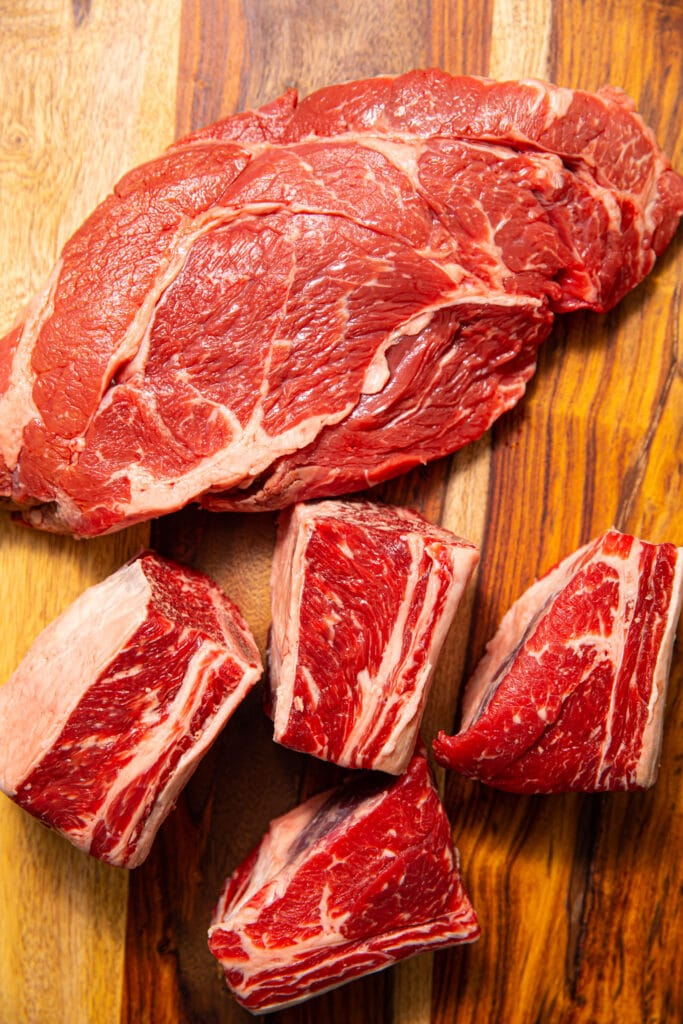 raw beef chuck roast and short ribs on wood cutting board