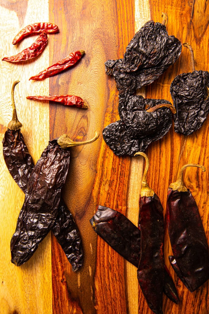 dried Chile pods on wood cutting board
