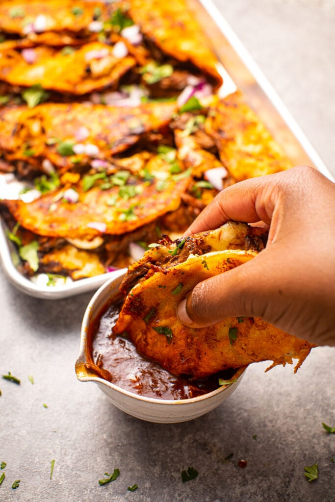 black hand dipping birria taco into consomé