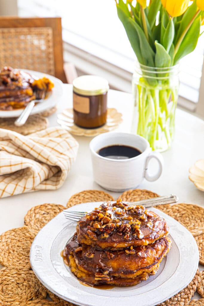 sweet potato pancakes on white plates with flowers in the background