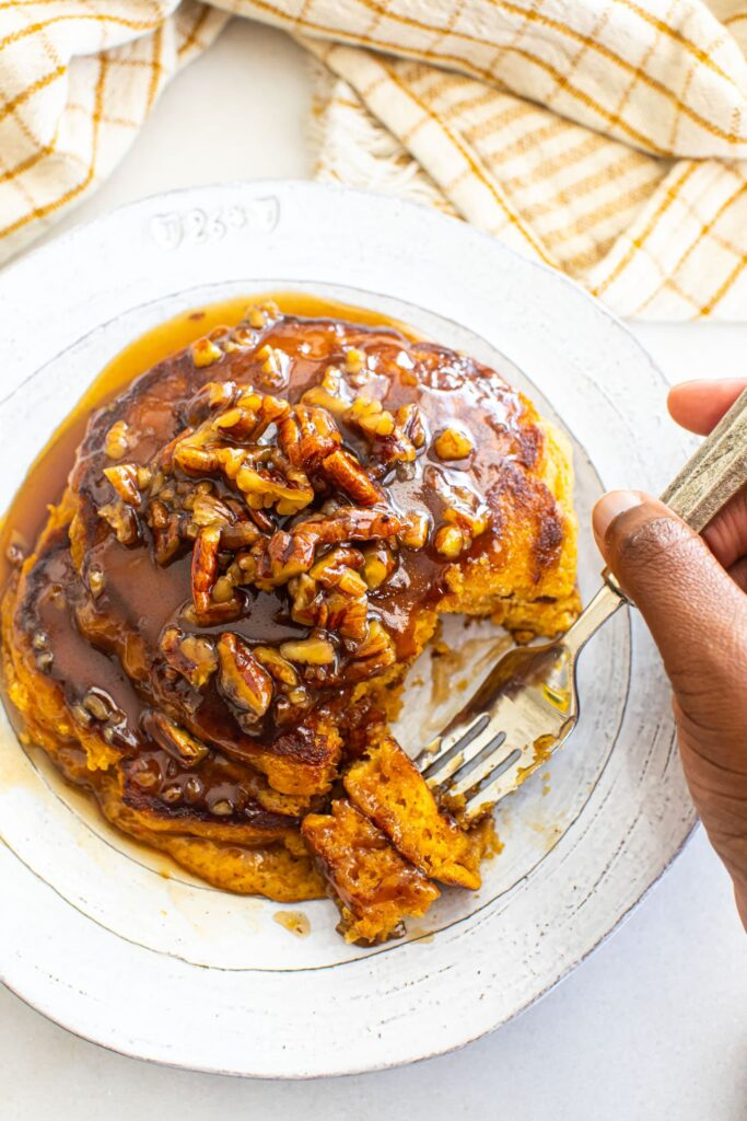black hand taking a forkful of sweet potato pancakes on white plate