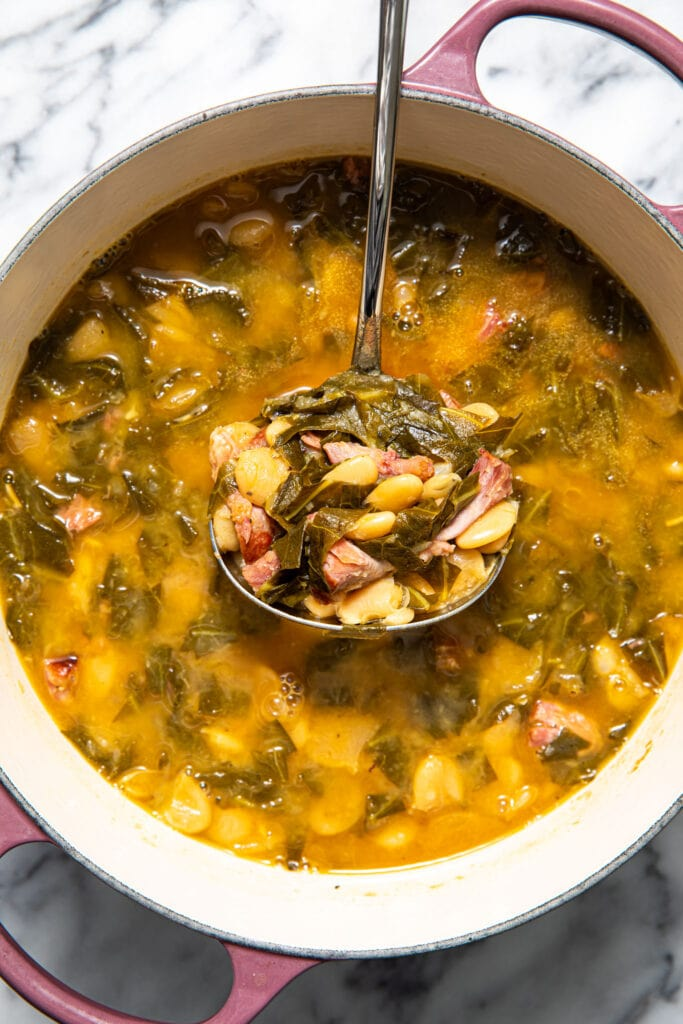 collard greens soup with beans and ham in large purple pot