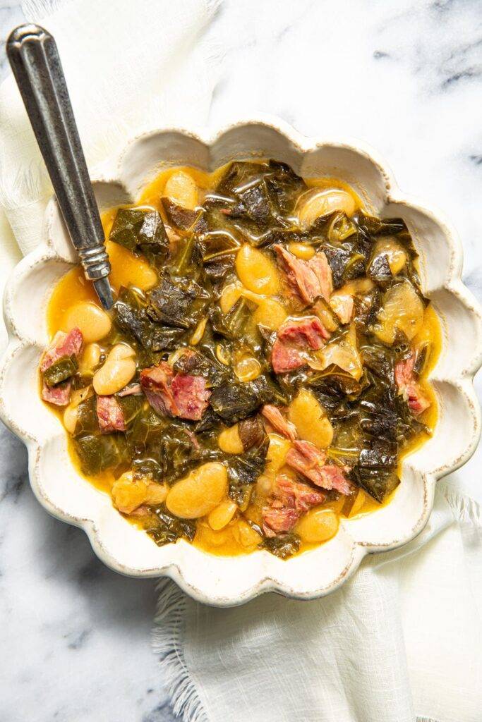 collard greens soup in scalloped bowl on marble surface