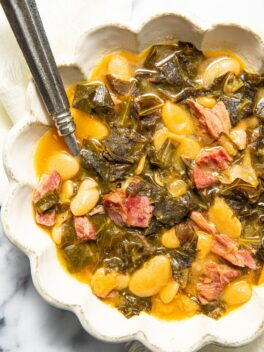 collard greens soup with beans and ham in scalloped bowl with spoon