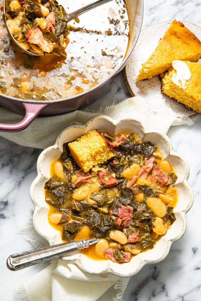 collard greens soup with beans and ham in bowl on marble surface with pot