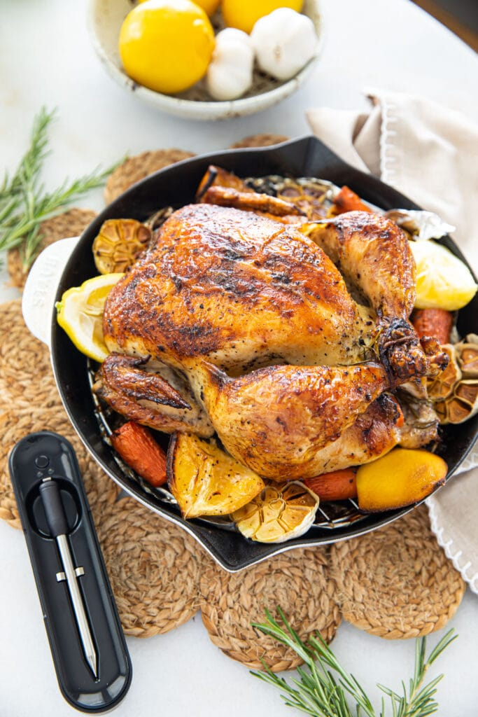 roast chicken in white skillet with meat thermometer on the side