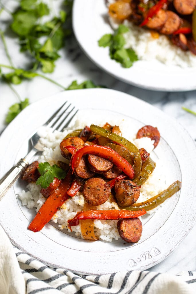 sausage and peppers on top of white rice on white skillet