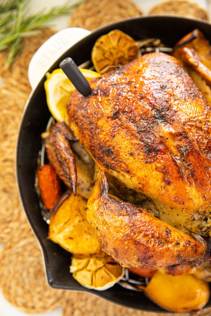 meat thermometer in breast of roast chicken in white skillet