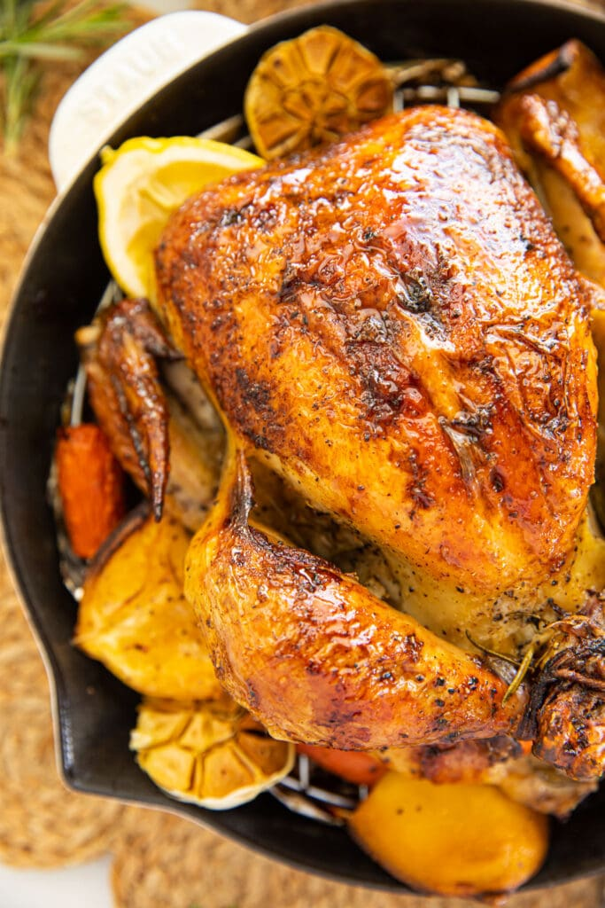 roast chicken with lemons and vegetables in white skillet on table mat