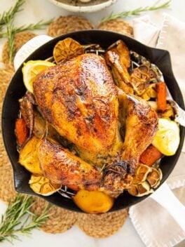 lemon garlic butter roast chicken in white skillet on table