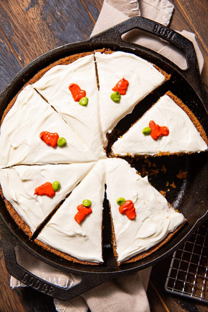 sliced carrot cake in black cast iron skillet on wood surface