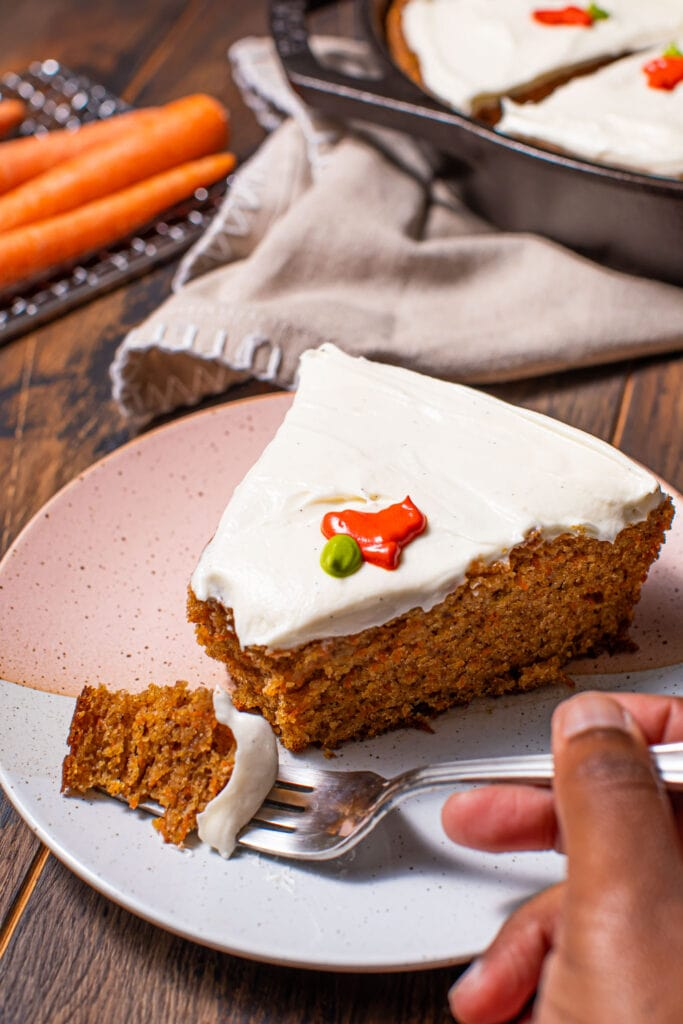 black hand taking forkful of carrot cake on pink and white plate