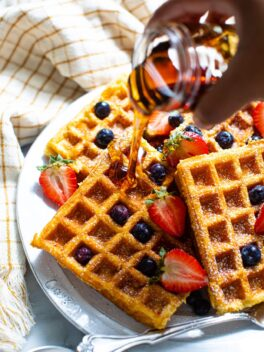 black hand pouring syrup over buttermilk waffles and fruit