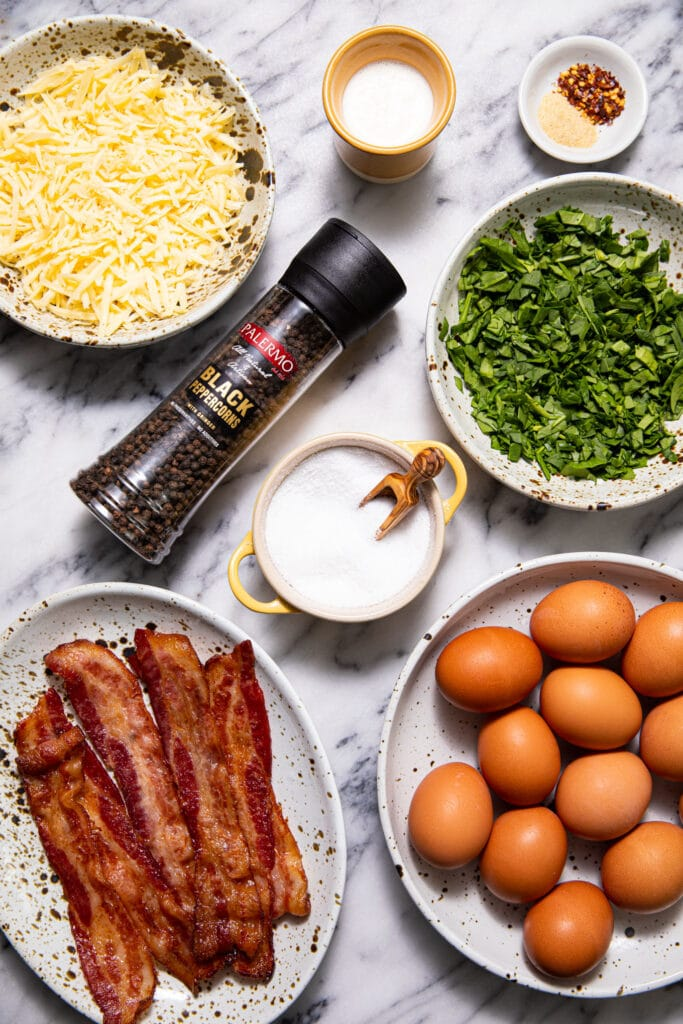 ingredients for bacon and gouda egg bites on marbled surface