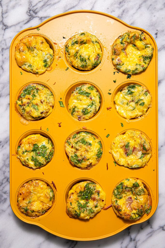bacon, gouda, and spinach egg bites in yellow muffin tray