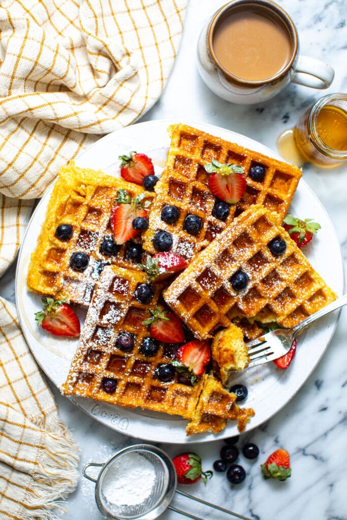 buttermilk waffles with fruit on plate on marble surface