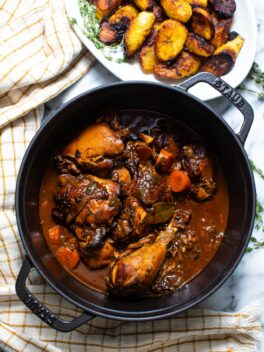 brown stew chicken in black pot with yellow striped linen