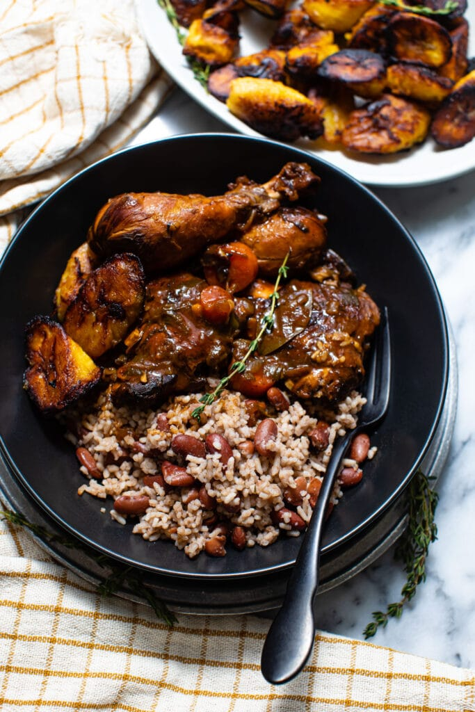 brown stew chicken with rice and peas in black bowl with black fork
