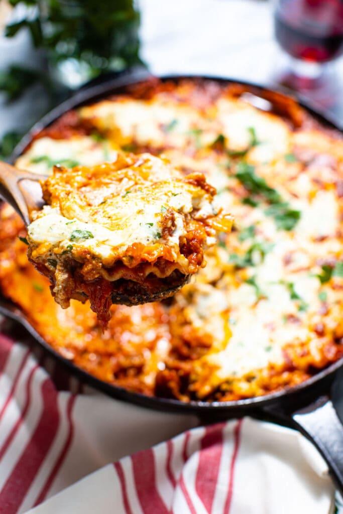 piece of lasagna on wooden spoon