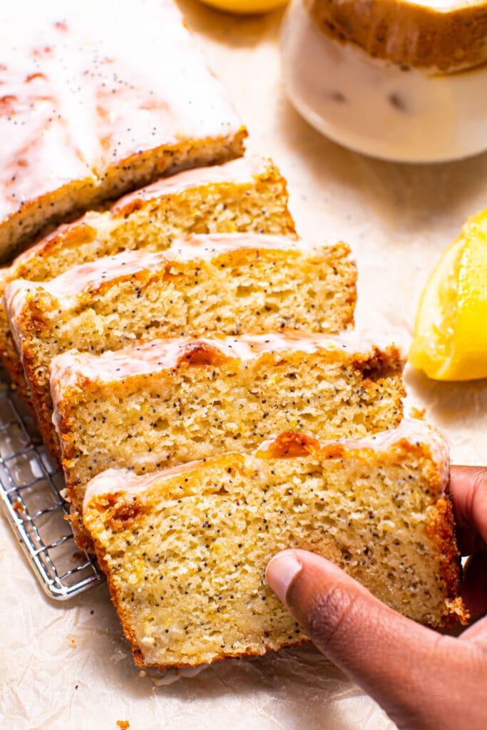 black hand grabbing a slice of lemon poppy seed bread