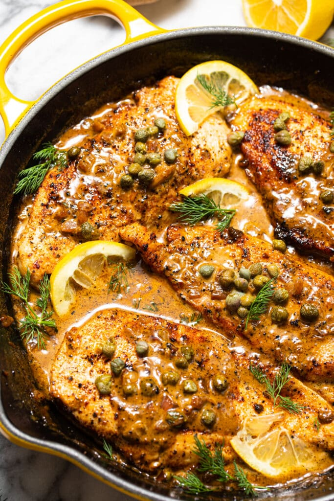 chicken with caper cream sauce in yellow skillet