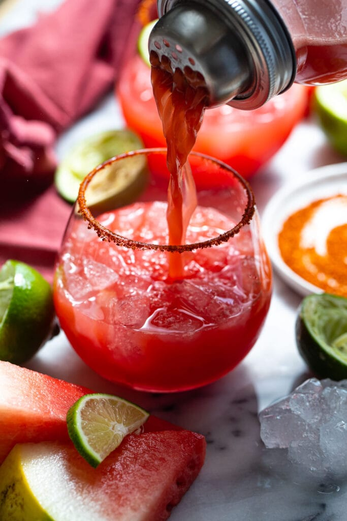 watermelon margarita being poured into a glass