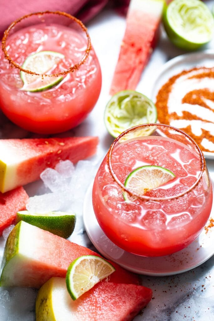 two watermelon margaritas on marble surface with slices of watermelon