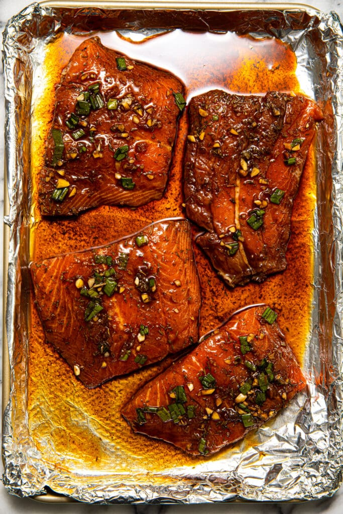 uncooked jerk salmon on baking sheet with foil