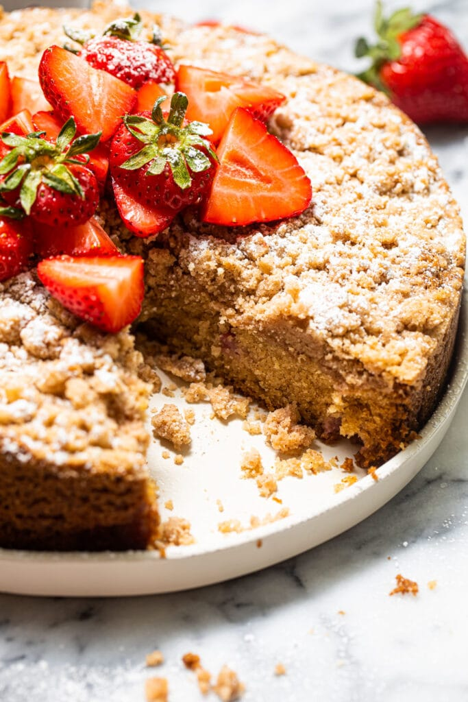 strawberry crumb cake with sliced strawberries on white plate