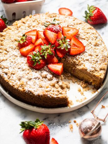 strawberry crumb cake on white plate with dusting wand on the side