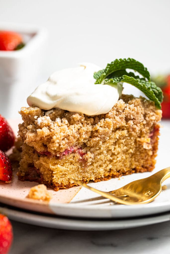 slice of strawberry crumb cake with whipped cream on small plate
