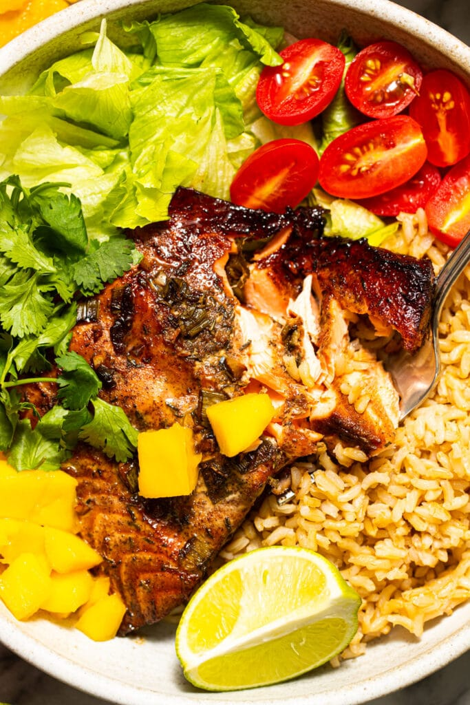 close up of jerk salmon with rice, lettuce, tomatoes, and chopped mango in bowl